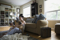 Woman cuddling dog and watching TV living room - HEROF25927