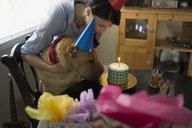 Woman and dog celebrating birthday with cake - HEROF25942