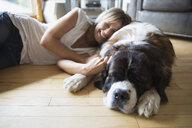 Woman laying sleeping dog living room floor - HEROF25957
