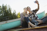 Smiling young couple taking selfie dock near canoe - HEROF25981