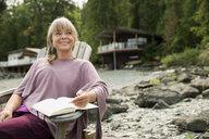 Smiling woman reading book outside lake house cabin - HEROF26002