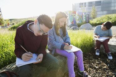 Students doing homework on rocks at sunny playground - HEROF26032