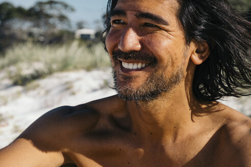 Close-up of happy shirtless man looking away while sitting at Hyams Beach during sunny day - CAVF60799