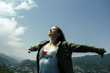 Happy woman with arms outstretched standing on mountain against blue sky during sunny day - CAVF60808
