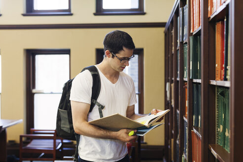 Confident man with backpack reading book while standing by shelf in library - CAVF60814