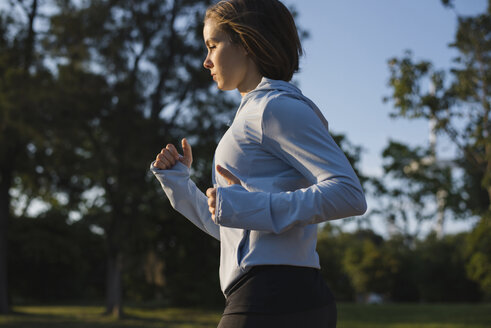 Side view of confident woman jogging while exercising in park - CAVF60826