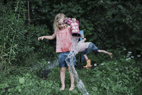 Full length of sister pouring water from rubber boot while brother amidst plants at park - CAVF60847