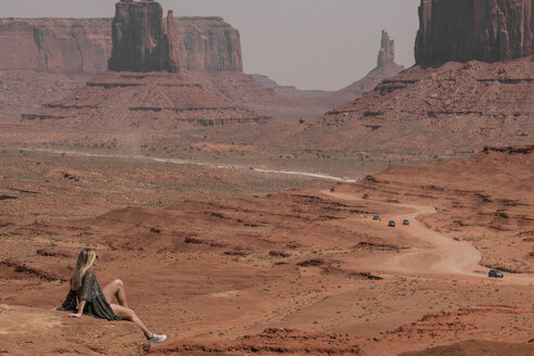 Side view of female hiker looking at buttes while sitting on rocks in Monument Valley Tribal Park during sunny day - CAVF60916