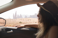 Side view of woman wearing hat and sunglasses while sitting in car at Monument Valley Tribal Park - CAVF60919