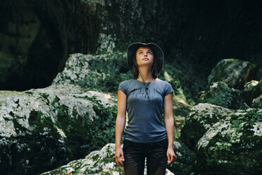 Woman wearing hat looking up while standing against rock formations - CAVF60943