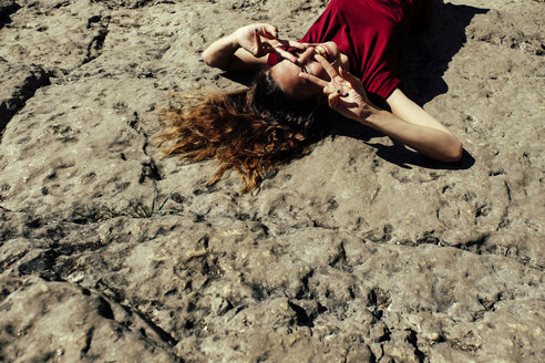 High angle view of happy woman gesturing while lying on rock formation during sunny day - CAVF60946