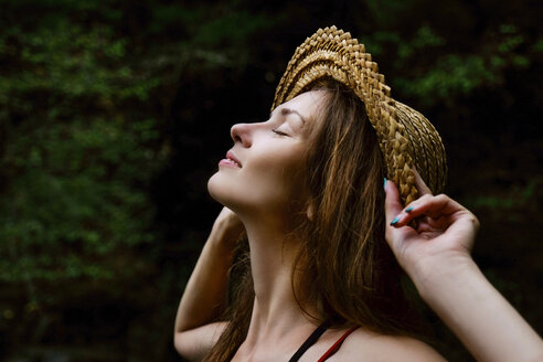 Close-up of smiling woman wearing hat while standing against trees in forest - CAVF60949