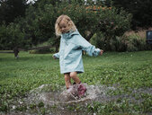 Playful girl splashing water in puddle at apple orchard - CAVF60994
