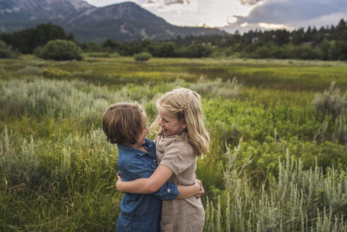 Happy sisters looking at each other while embracing on grassy field in forest during sunset - CAVF61006