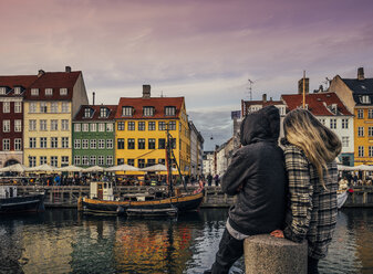 Couple enjoying view of canal and colorful buildings, Copenhagen, Denmark - CAIF22619