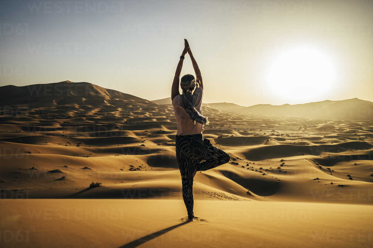 Serene woman standing in yoga tree pose in sunny sandy desert, Sahara, Morocco - CAIF22622 - Anna Wiewiora/Westend61