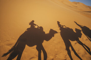 Shadows of people riding camels in sandy desert, Sahara, Morocco - CAIF22625