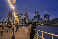 Couple standing along Thames River, London, UK - CAIF22628