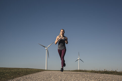 Young woman jogging on field way, wind wheels in the background - SEBF00001