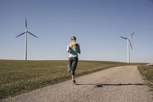 Young woman jogging on field way, wind wheels in the background - SEBF00004
