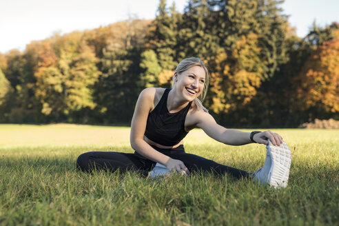 Young woman stretching her leg on a meadow - SEBF00013