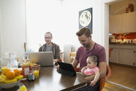 Homosexual couple using technology with baby daughter table - HEROF26047