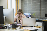 Focused businesswoman working at desk in office - HEROF26098