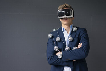 Businessmanman wearing VR glasses and mirror ball fairy lights - MOEF02078