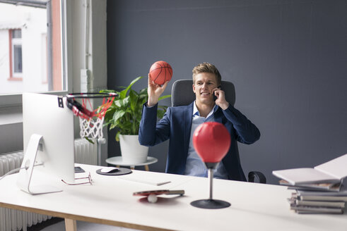 Young businessman sitting at desk in office playing basketball and talking on cell phone - MOEF02081