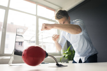 Young businessman at desk in office boxing with punching ball - MOEF02096