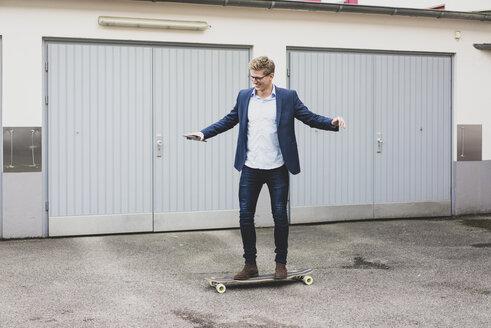 Young businessman riding skateboard at garage door - MOEF02102
