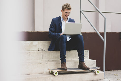 Happy young businessman with skateboard sitting outdoors on stairs using laptop - MOEF02114