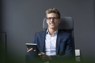Smiling young businessman sitting on office chair using tablet - MOEF02132