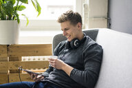 Smiling young man with tablet and headphones sitting on couch - MOEF02135