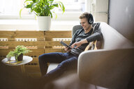 Smiling young man with guitar, tablet and headphones sitting on couch - MOEF02138