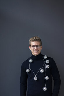Portrait of smiling young man wearing mirror ball fairy lights - MOEF02141