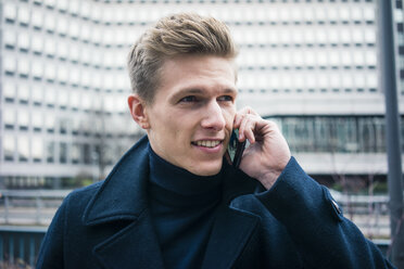 Portrait of smiling young man talking on cell phone in the city - MOEF02150