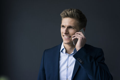 Portrait of smiling young businessman on cell phone - MOEF02156