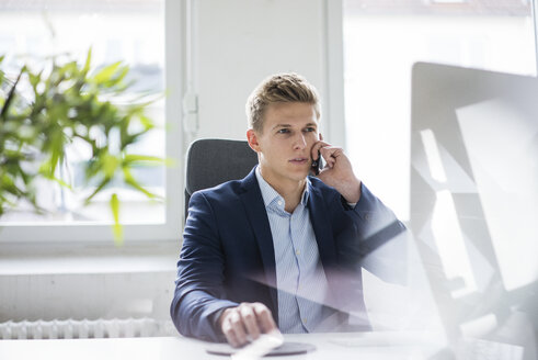 Young businessman sitting at desk in office talking on cell phone - MOEF02159
