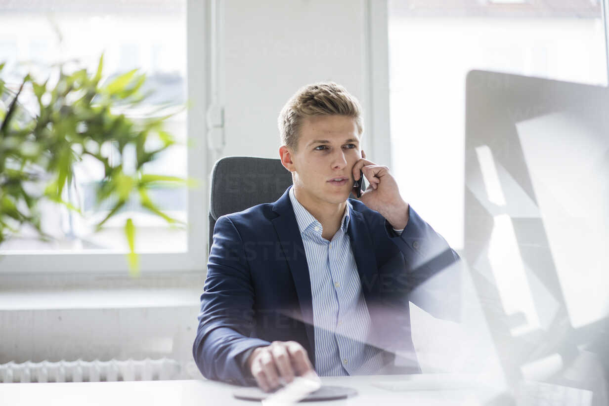 Young businessman sitting at desk in office talking on cell phone - MOEF02159 - Robijn Page/Westend61