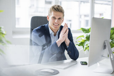 Portrait of confident young businessman sitting at desk in office - MOEF02162