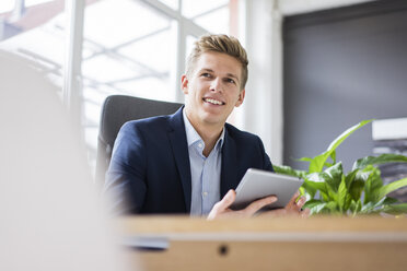 Confident young businessman sitting at desk in office using tablet - MOEF02165