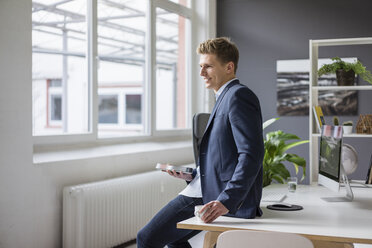 Smiling young businessman sitting on desk in office having a coffee break - MOEF02168