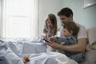 Father and children using digital tablet in bed - HEROF26160