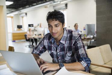 Businessman working at laptop in office - HEROF26202