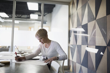 Businesswoman reviewing paperwork in conference room - HEROF26205