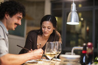 Couple eating with chopsticks and drinking white wine in apartment kitchen - CAIF22662