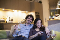 Happy couple drinking white wine and watching TV on apartment sofa - CAIF22683