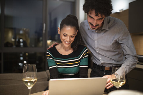 Smiling couple using laptop and drinking white wine at home at night - CAIF22689