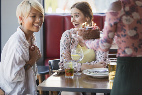 Excited young women friends celebrating birthday with cake in restaurant - CAIF22705